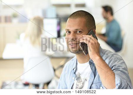 Portrait of office-worker talking on phone
