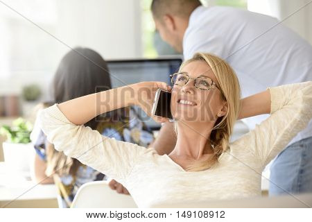 Relaxed woman in office talking on phone