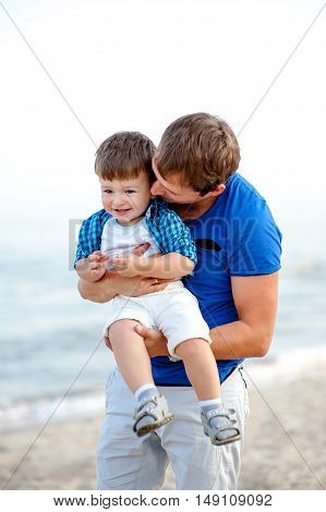 Men hug a boy on the sea and have fun on a bright sunny day