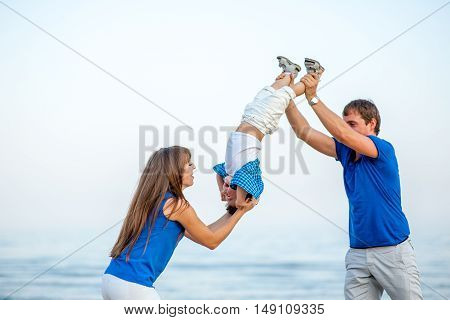 Men and woman shake a boy on the sea and have fun on a bright sunny day