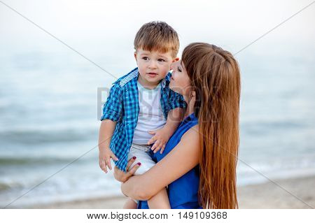 Woman hugs a boy on the sea and have fun on a bright sunny day