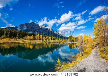 Canmore, near Banff Park. Path around the lake. The concept of hiking. Mountains and autumn aspens reflected in the water