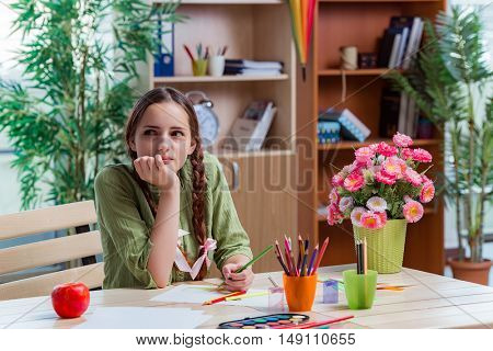 Young girl drawing pictures at home