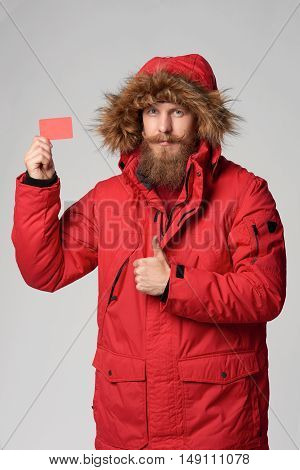 Portrait of a man wearing red winter jacket with hood on showing blank credit card and gesturing thumb up, studio shot