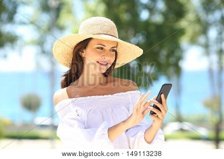 Happy fashion woman wearing picture hat texting on phone in summer with the sea in the background