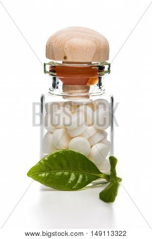 White pills in clear glass container with wooden top and green leaf on white background
