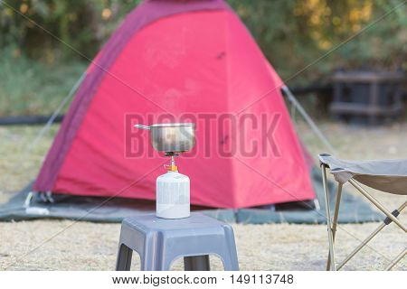 Cooking with gas stove in camping site. Selective focus on gas burner pot and smoke from boiling water. Tent in the background out of focus. Outdoor activities.