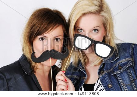 Young women are joking with artificial moustache and paper glasses. Isolated with light background.