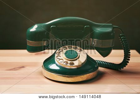 Old telephone on the table, black background