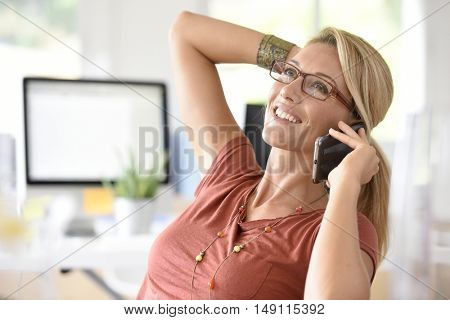 Attractive blond middle-aged woman talking on phone
