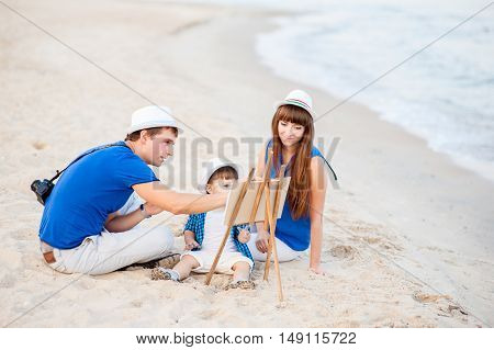 Woman man and child in blue and white dress sit on the beach and draw on the easel near the surf