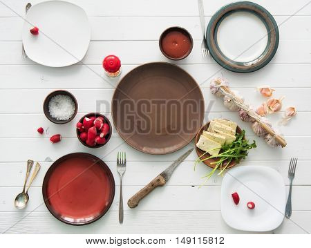 white wooden table served for four with empty plates, radish and garlic, top view