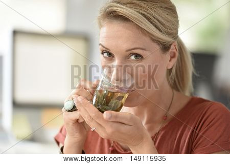 Attractive woman designer drinking tea in office