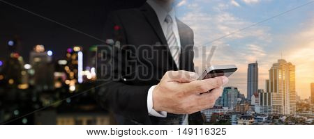 Businessman using mobile phone with panoramic night and day cityscape of Bangkok city