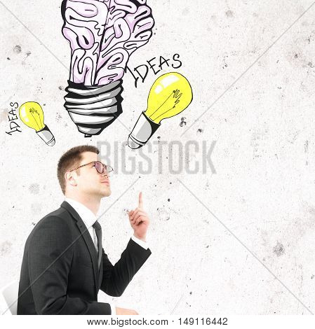 Handsome businessman in glasses pointing at creative light bulb brain sketch. Ideas and brainstorming concept