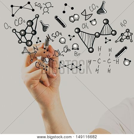 Male hand writing chemical formulas on light background