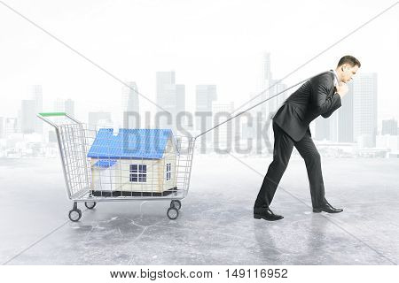 Businessman dragging trolley with blue house on city background. Property shopping concept. 3D Rendering
