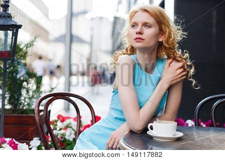 young red-haired girl in blue dress at table in outdoor cafe