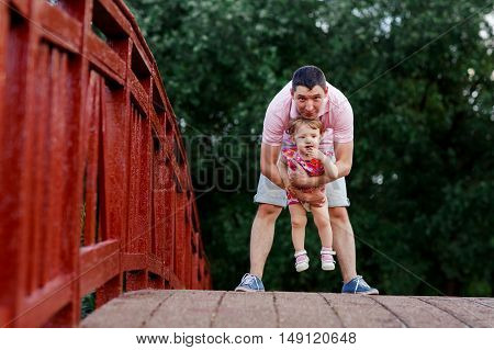 Dad with his little daughter standing on large wooden bridge