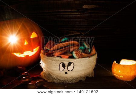 halloween composition with pumpkin head jack lantern sweets looks like brain in mummy bowl and orange candle on wooden background