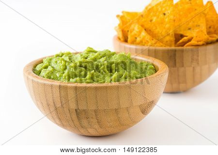 Guacamole and nachos in a wooden bowl isolated on white background