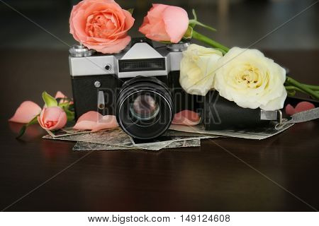 Vintage camera and beautiful roses on wooden table