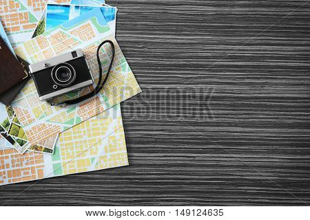Vintage camera, map and passports on wooden table