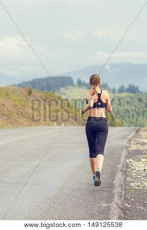 Young Slim Woman Running On Mountain Road