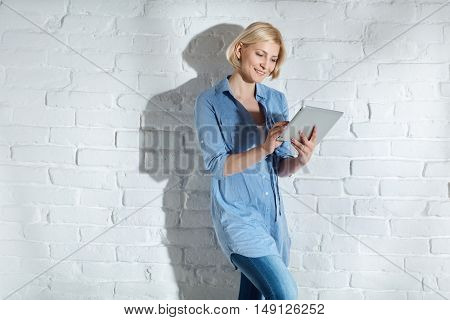 Casual young woman standing by wall, using tablet computer, smiling.