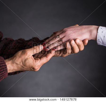 Old Man Holding Young Woman's Hand