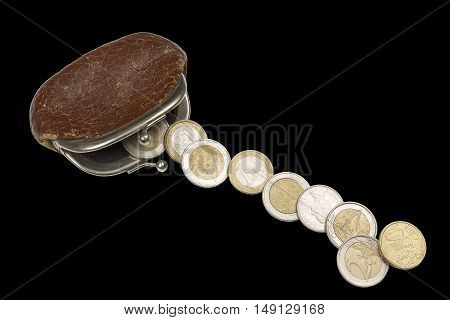 Vintage brown change purse and euro coins isolated on black background.