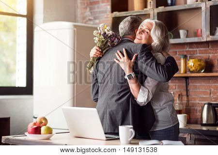 Love you Husband hugging his beautiful wife while she smiling and hoilding flowers