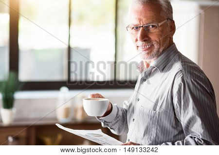 Good morning to you Caucasian male in glasses standing with his white cup in his kitchen