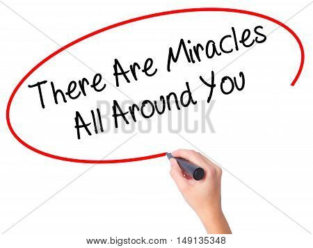 Women Hand Writing There Are Miracles All Around You  With Black Marker On Visual Screen