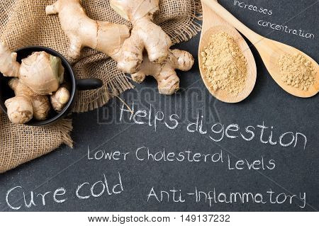 Composition of ginger on a stone countertop and inscriptions mentioning its advantages