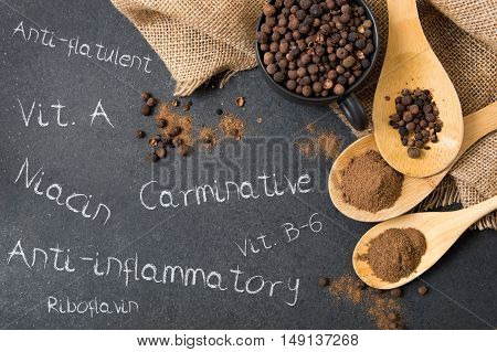 Composition of allspice on a stone countertop and inscriptions mentioning its advantages