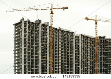 Crane and building construction on sky background