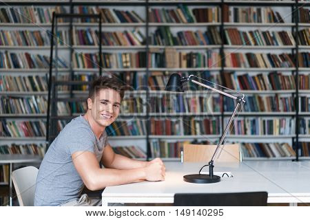 Smiling man with book in library