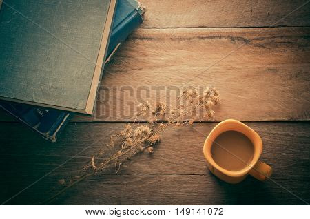Orange coffee cup on the wood table with book- tone vintage