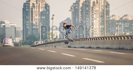 Skater Doing Tricks And Jumping On The Street Highway Bridge. Panorama View