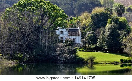 Landscape with a Cape Dutch House hidden away and a Pond
