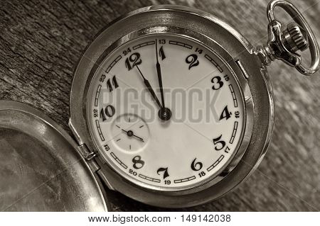Time concept - Vintage pocket watch on weathered wood background.