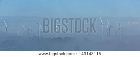 Landscape with wind turbines in the morning fog