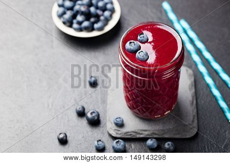 Berry smoothie with fresh blueberries on a black stone background Copy space