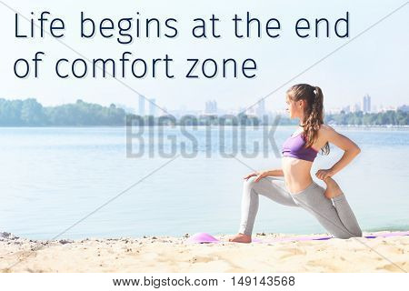Comfort zone concept. Attractive young woman doing yoga by the river