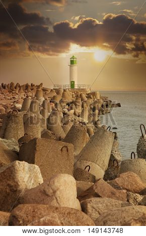 Lighthouse at sunset on the background of dramatic sky in Ventspils Latvia