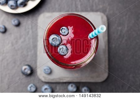 Berry smoothie with fresh blueberries on a black stone background Copy space Top view