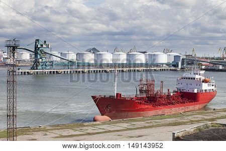 A large red ship docked on a sunny summer day in the port of Ventspils Latvia