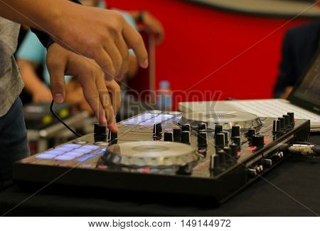 Dj mixes and playing the track controller turntable. New digital DJ technology for mixing audio tracks from notebook or flash drive.