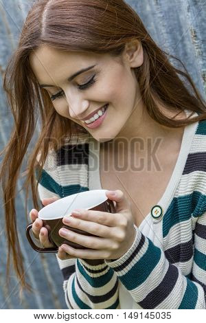 Outdoor portrait of happy beautiful girl or young woman with red hair laughing and drinking coffee